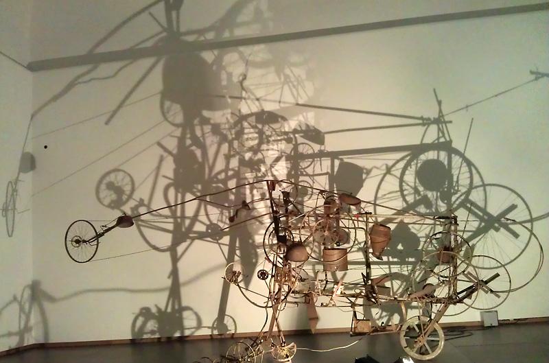 Machine van Tinguely op de tentoonstelling werpt schaduwen. Foto auteur