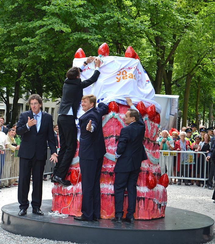 2014: Koning Willem-Alexander onthult een taart bij de expo Grandeur met Franse beeldhouwkunst, maar het doek wil er niet goed af. Directeur Jan Teeuwisse van Beelden aan Zee (links) kijkt verontschuldigend.