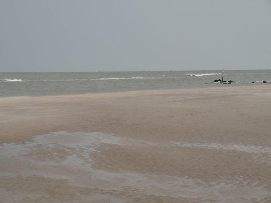 Strand en zee met een schip aan de horizon